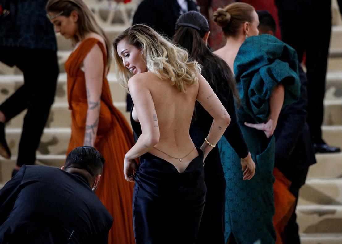 La cantante Miley Cyrus, con un provocador vestido hasta donde la espalda pierde su nombre, deStella McCartney.