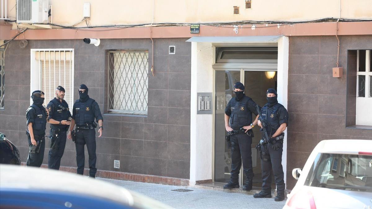 Miembros los mossos custodian la entrada de la vivienda del agresor de la comisaría de Cornellà.