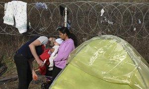 Un migrante besa a un bebé en Pazarkule, cerca de la frontera turco-griega.