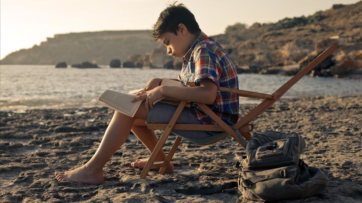 Un niño leyendo en la playa.