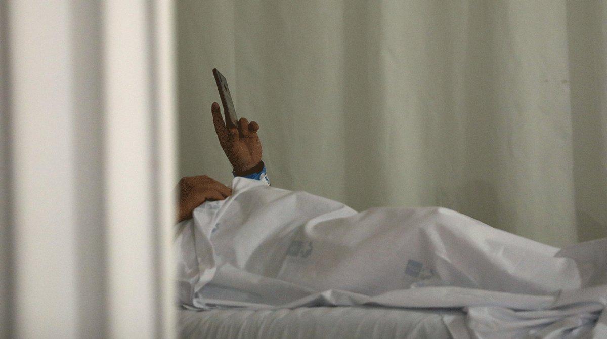 Un paciente del Hospital Infanta Sofía de Madrid consulta su teléfono móvil, el 8 de mayo.
