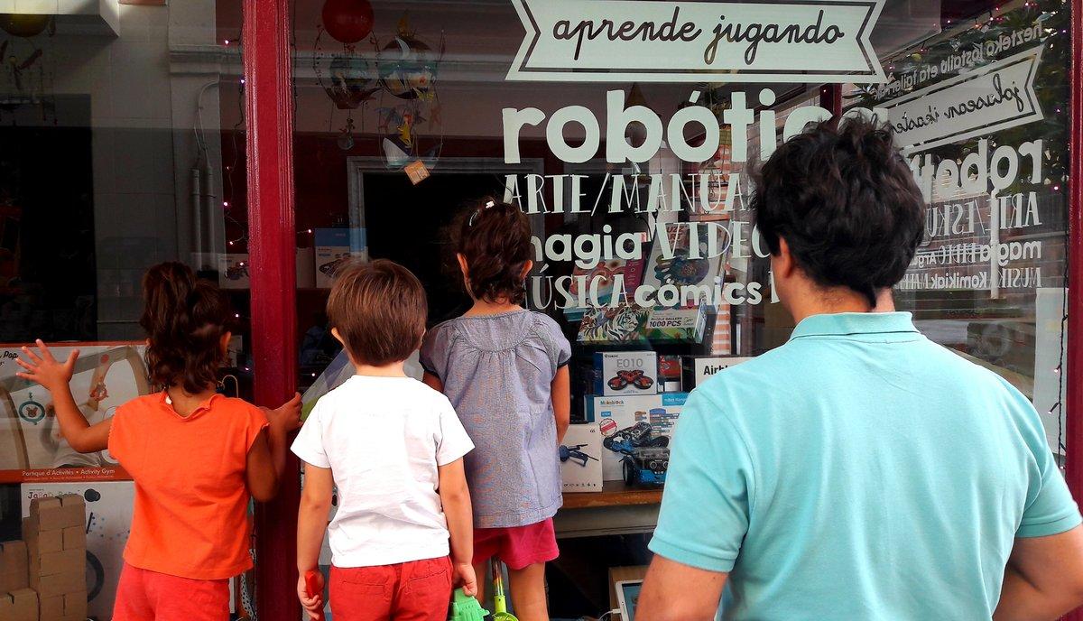 Un padre mira con sus hijos el escaparate de una tienda infantil de robótica