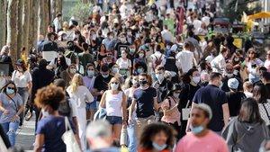Personas con mascarillas pasean por la Avenida de los Campos Elíseos en París.