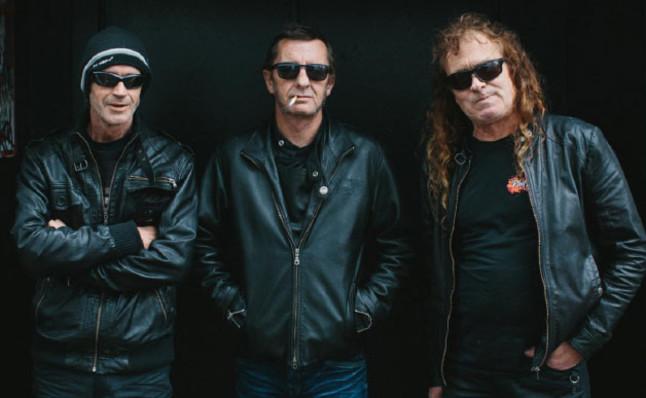 Phil Rudd, en el medio, posando con los miembros de su banda.