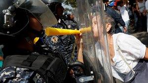 Una manifestantes de la oposición se encara con los antidisturbios en la protesta de este sábado en Caracas.