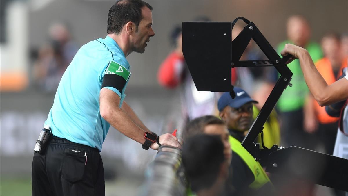 Un árbitro de la Bundesliga consulta el VAR en un partido de esta temporada.