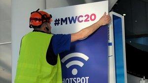 Un trabajador coloca un cartel informativo del Mobile World Congress de este año, en el recinto ferial donde se celebra el congreso.