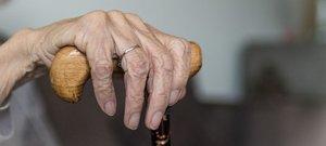 Una anciana se apoya en su bastón.