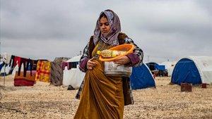 Una mujer embarazada camina por el campo de Washukanni, en el norte de Siria.