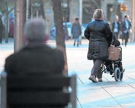 Una mujer pasea a su marido en silla de ruedas, en Barcelona.