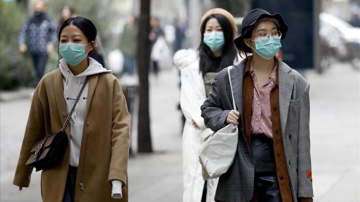 Unas mujeres asiáticas pasean por el centro de Milán con unas mascarillas médicas