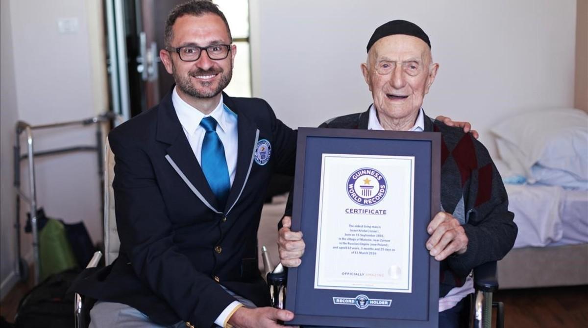 Yisrael Kristal (derecha) recibe el certificado que le acredita como el hombre más viejo del mundo, en Haifa (Israel), este viernes.