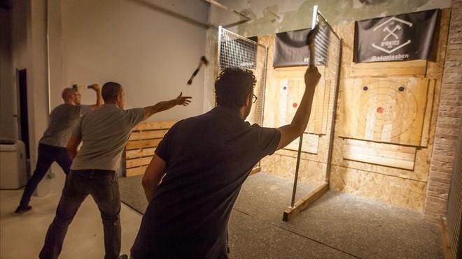 Tres chicos tiran hachas en Barcelona Axe Throwing.
