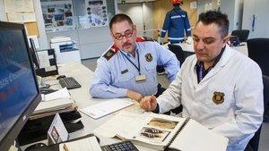 El agente Ubaldo (con bata) y elsubinspector Antón revisan el informe.