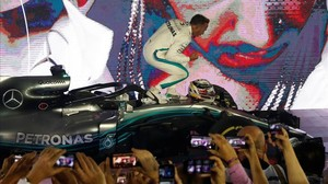 El britániico Lewis Hamilton celebra, frente a los mecánicos del equipo Mercedes, su triunfo de hoy en Singapur.
