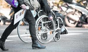 Un ciudadano cruza el paso de peatones en silla de ruedas.