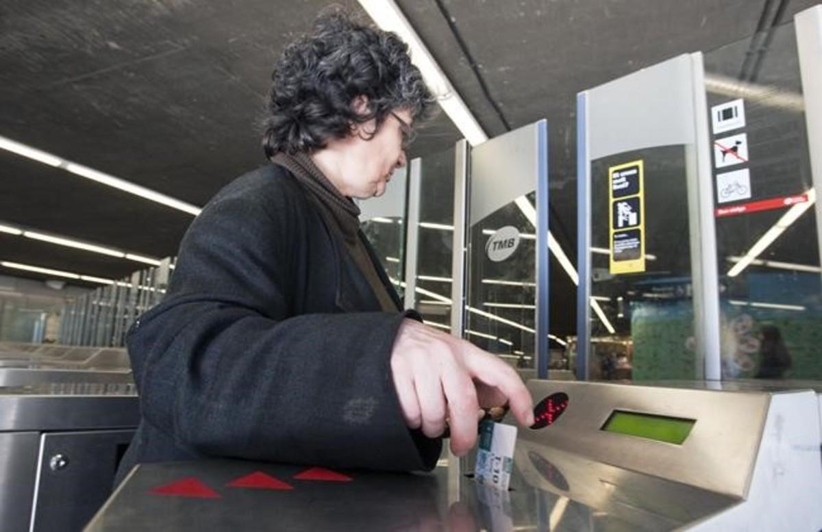 Una mujer valida su billete en una estación de metro de Barcelona.
