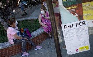Mujeres con mascarilla conversan en una calle de Ripollet.