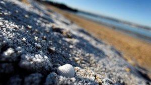 La escarcha cubre parte de la arena de la playa de Praia Grande de Mino, en Galicia.
