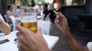 Una persona sostiene un cigarrillo en una terraza.