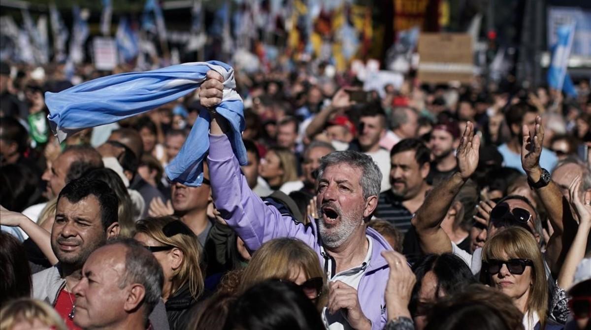 Un hombre empuña la bandera argentina entre la multitud que ha tomado las calles de Buenos Aires para protestar por la situación económica del país.