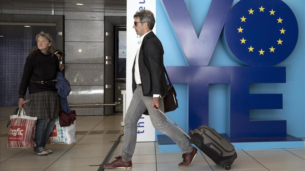 Un hombre pasa junto a un anuncio llamando al voto en las elecciones europeas en el metro de Bruselas, este viernes.