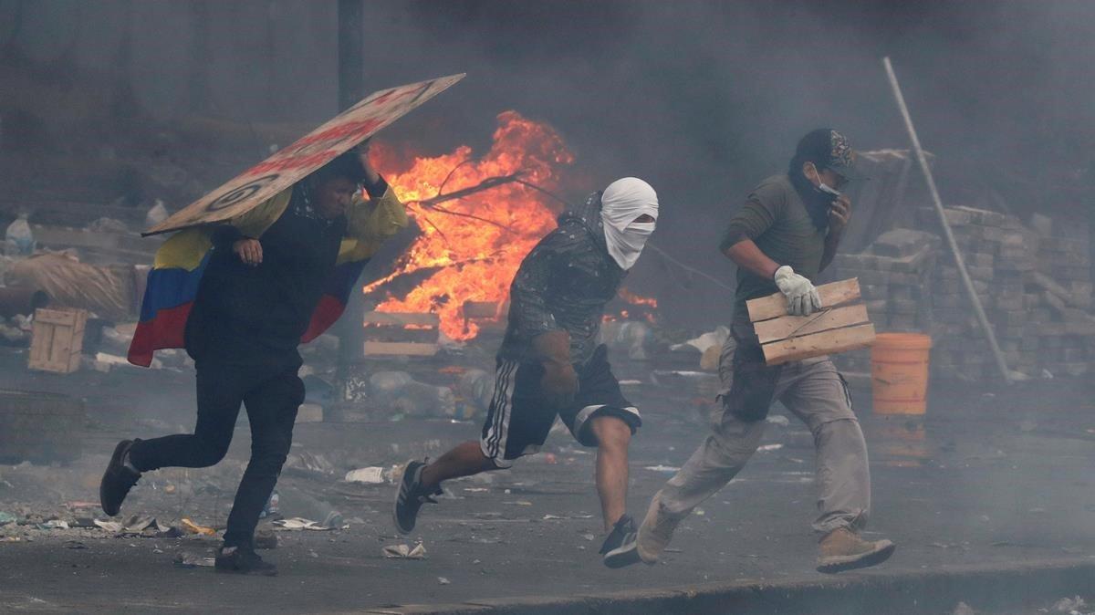 Indígenas ecuatorianos buscan refugio durante los enfrentamientos con las fuerzas del orden, en Quito.