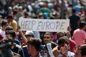 Un inmigrante se manifiesta este jueves en Budapestcon una pancarta en la que se lee Ayúdanos Europa.