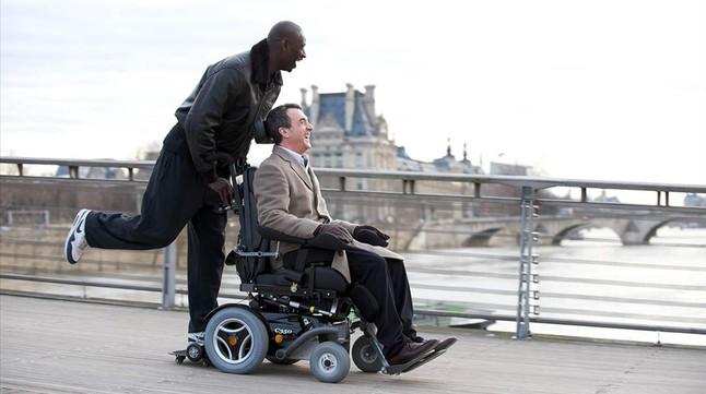 Omar Sy empuja la silla de ruedas de François Cluzet, en la película 'Intocable'.