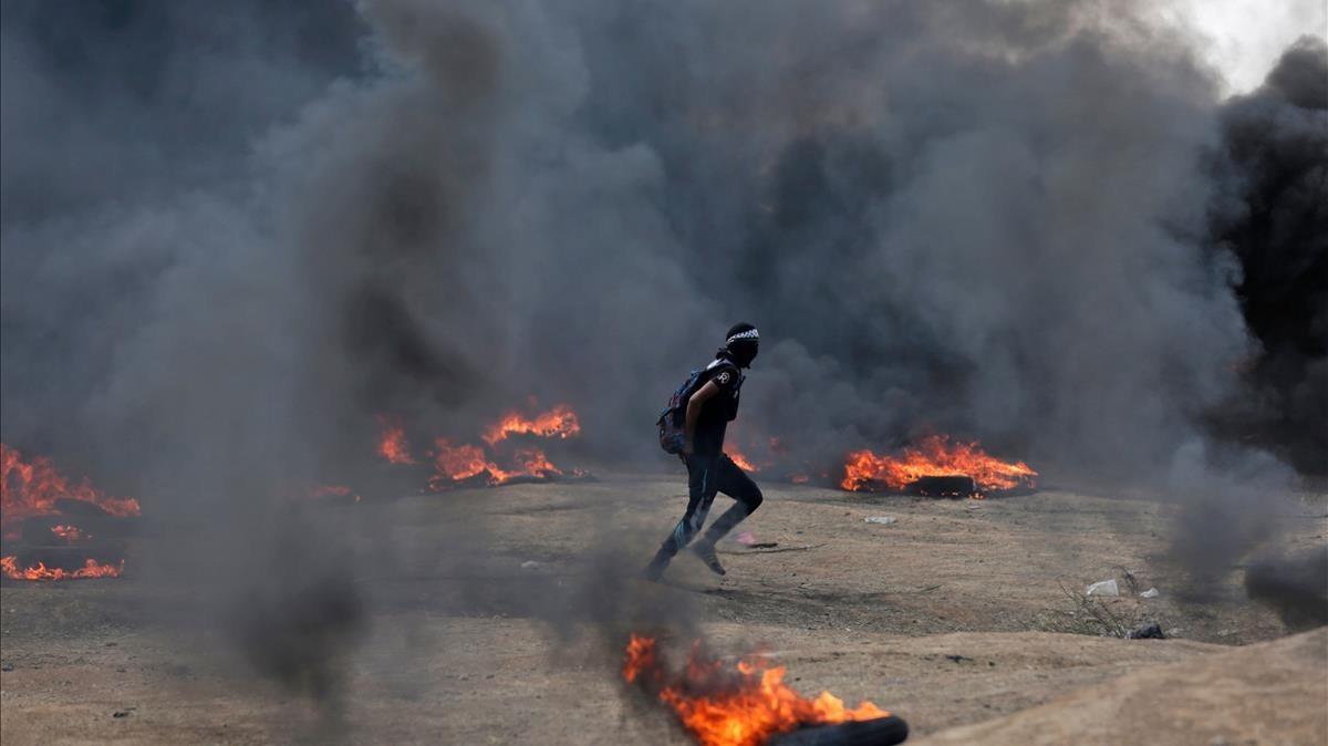 Un manifestante palestino corre entre las columnas de humo de neumáticos quemados en las protestas palestinasen la frontera de Gaza e Israel por el traslado de la embajada estadounidense a Jerusalén.