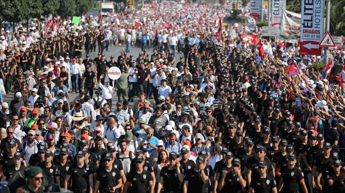 Kemal Kilicdaroglu, en el centro de la imagen, custodiado por la policía, camina el último kilómetro de la marcha con un letrero con la palabra Justicia escrita en turco.