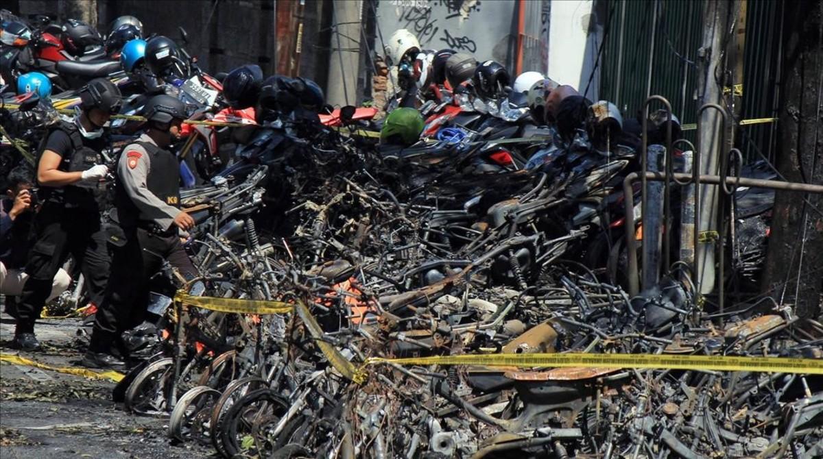 Miembros de las Fuerzas de seguridad indonesia inspeccionan los restos de la explosión de uno de los tres atentados que se han registrado en Surabaya.