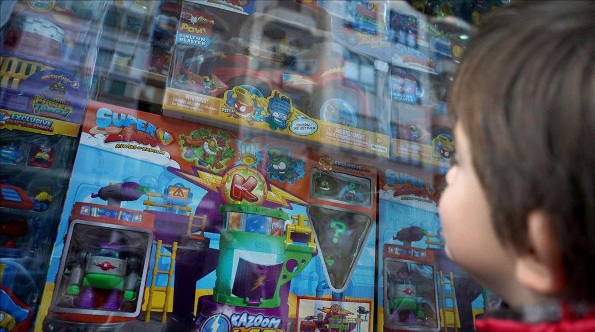 Un niño de cuatro observa el escaparate de una tienda de Madrid donde venden juguetes de Superzings