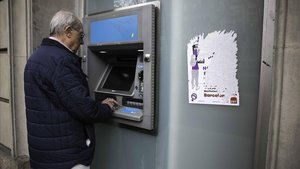 Un pensionista saca dinero de un cajero automático de una entidad bancaria de Barcelona, este viernes.