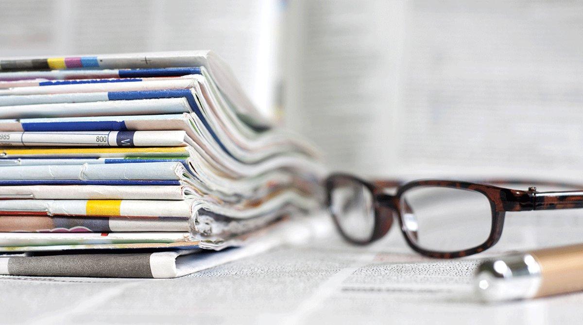Periódicos y revistas apilados en una mesa de trabajo.