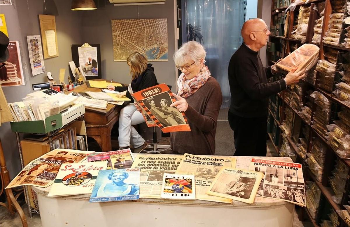 En primer plano, los fundadores de 'A la premsa d'aquell dia', Rosa Maria Urue y Roberto Costantini; atrás, a la izquierda, su hija Ágata, en el local.