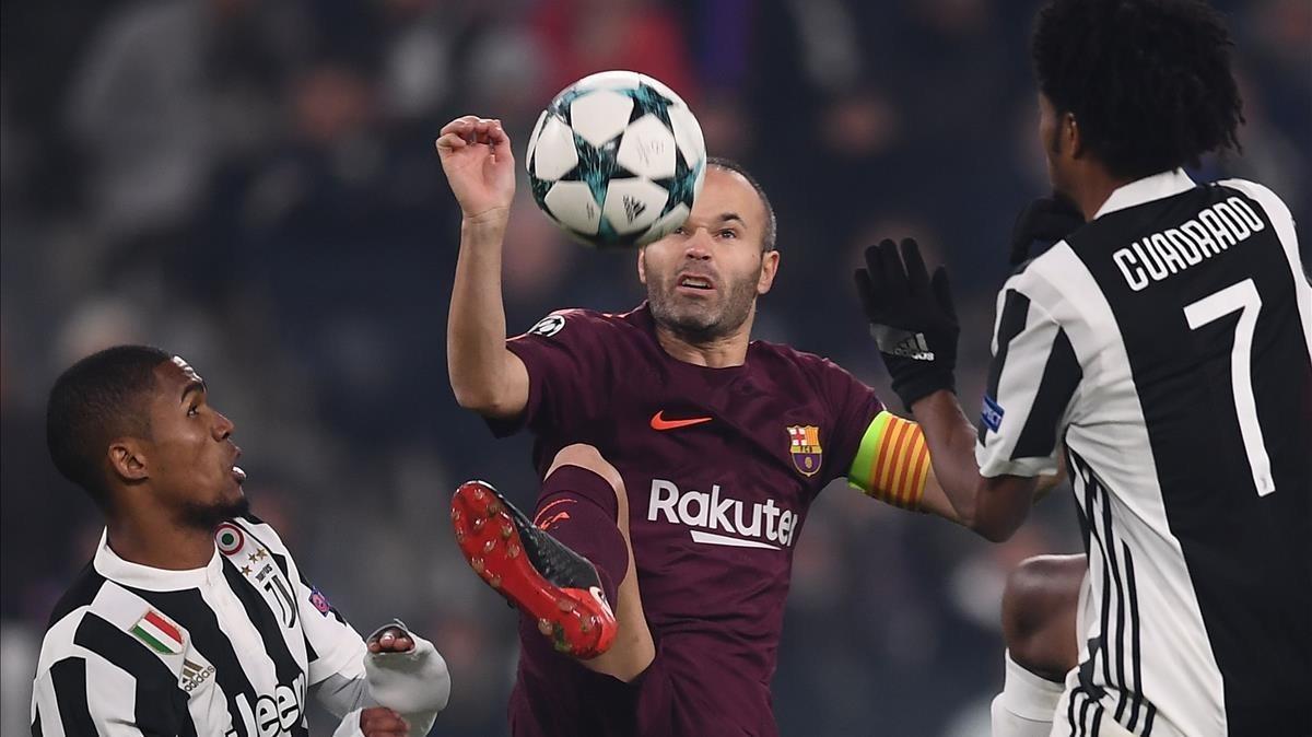 Iniesta controla un balón entre Douglas Costa y Cuadrado.