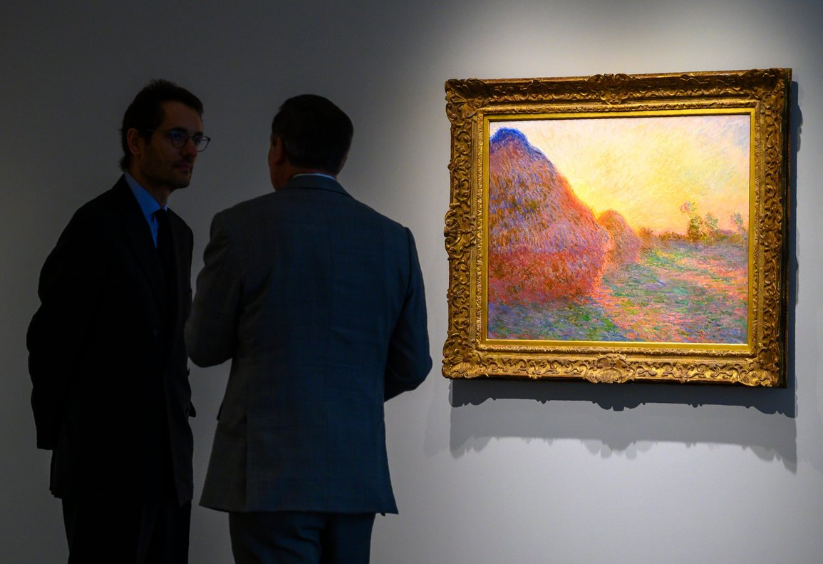 FILES In this file photo taken on May 02 2019 Sotheby s officials stand near one of Claude Monet s Meules during a media preview for Sotheby s Impressionist Modern Art and Contemporary Art auctions in New York - Monet s painting Haystacks Series Meules from 1890 was sold for 100 7 million at Sotheby s New York setting a record for Monet and for any work of Impressionist Art Photo by Don Emmert AFP RESTRICTED TO EDITORIAL USE - MANDATORY MENTION OF THE ARTIST UPON PUBLICATION - TO ILLUSTRATE THE EVENT AS SPECIFIED IN THE CAPTION