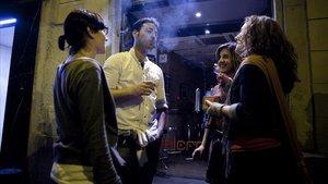 Un grupo de personas fumando en el exterior de un bar de la calle Vallfogona del barrio de Gracia.