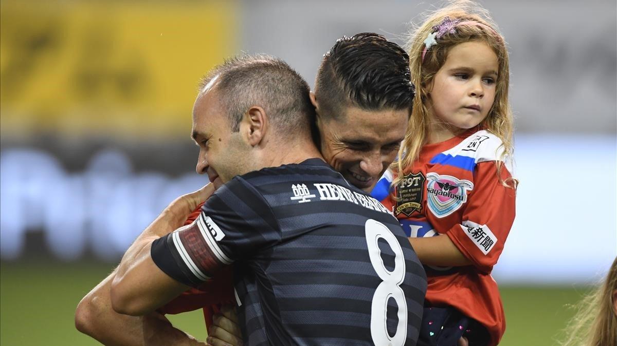 Torres se abraza a Iniesta en su último partido como profesional.