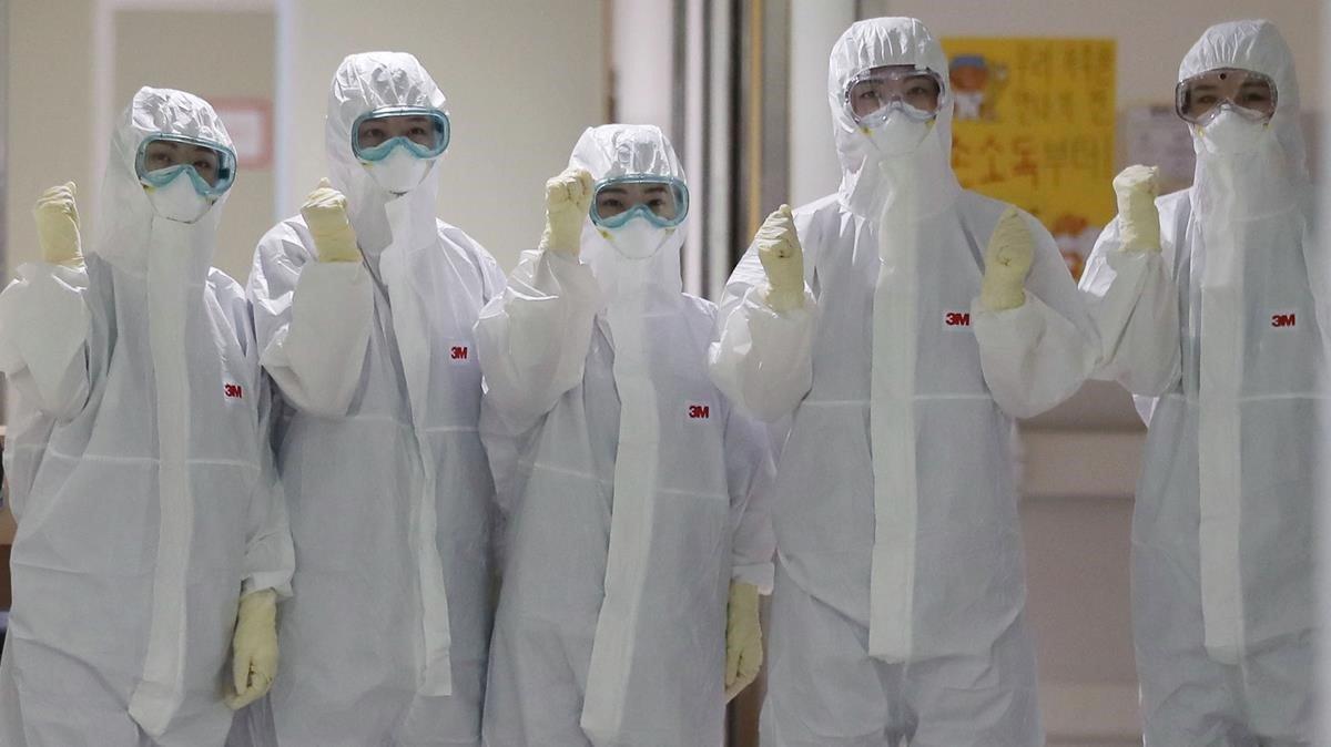 Trabajadores protegidos con trajes y máscaras en un centro médico de Bolivia.