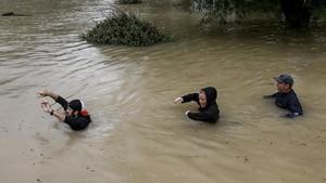 Tres personas cruzan un río de Houstoncerca del embalse de Addicks, que amenaza con desbordarse.