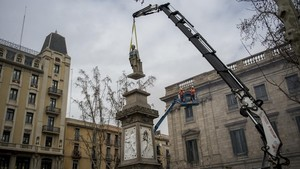 Una grúa levanta la estatua deAntonio López para bajarla de su peana, en la plaza que lleva su nombre, este domingo.