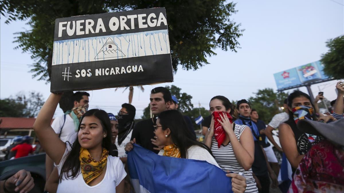 Una mujer sostiene un cartel contra Ortega durante una protesta antigubernamental, en Managua, el 11 de abril.