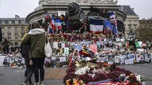 Unos jóvenes delante de uno de los homenajes del centro de París a las 130 víctimas del ataque terrorista del 13 de noviembre.