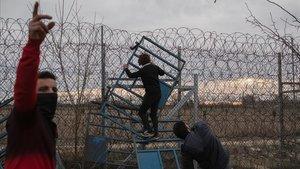 Unos refugiados intentan saltar la valla que separa Turquía de Grecia en Pazarkule, este viernes.