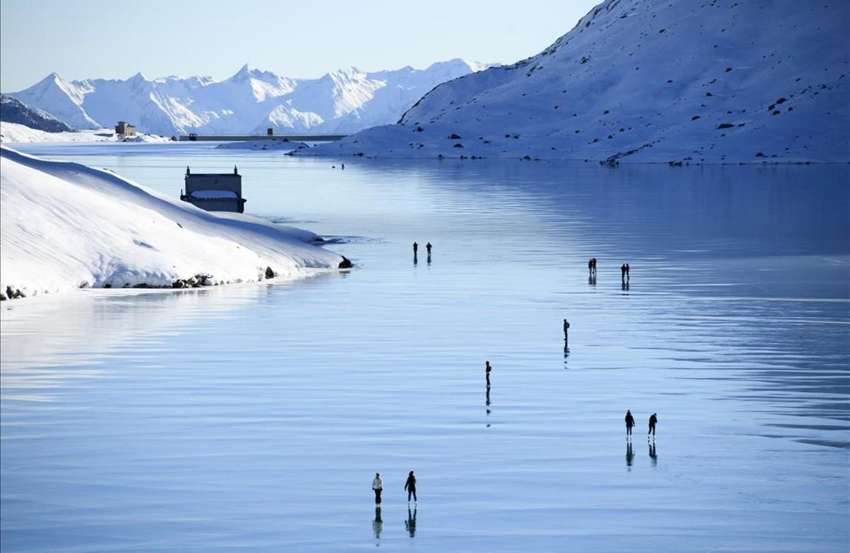 Visitants disfruten d'un dia assolellat al 'gel negre' del llac Bianco, a Poschiavo (Suïssa).