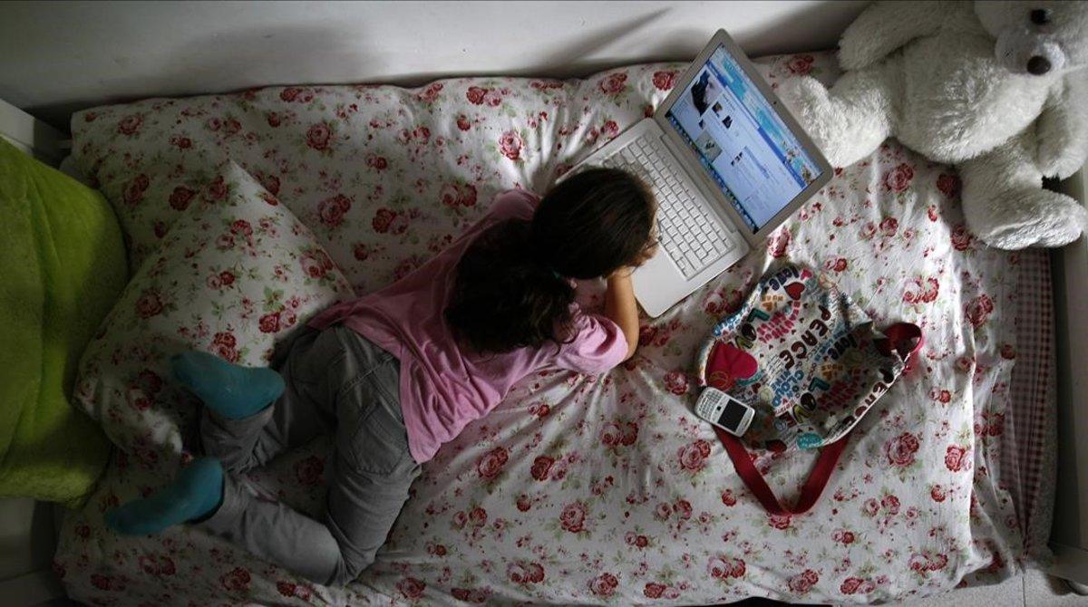 Una niña de 12 años navega en redes sociales desde la habitación de su casa.