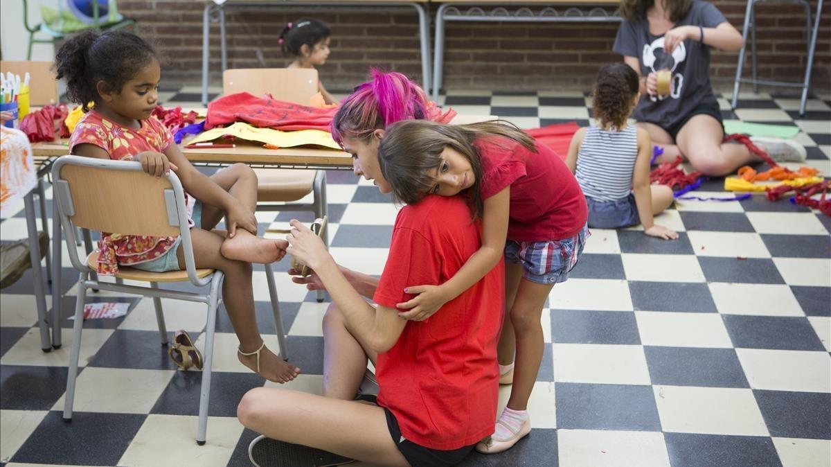 Una niña abraza a su monitora en un campamento urbano en el barrio de Baró de Viver de Barcelona, en el verano del 2016.