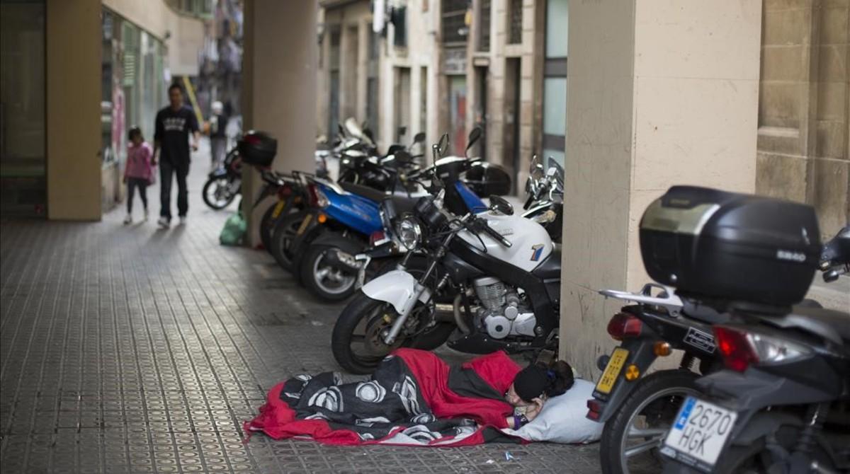 Una niña de camino al colegio se cruza con una mujer durmiendoen el suelo enla calle deEn Roig, este jueves.